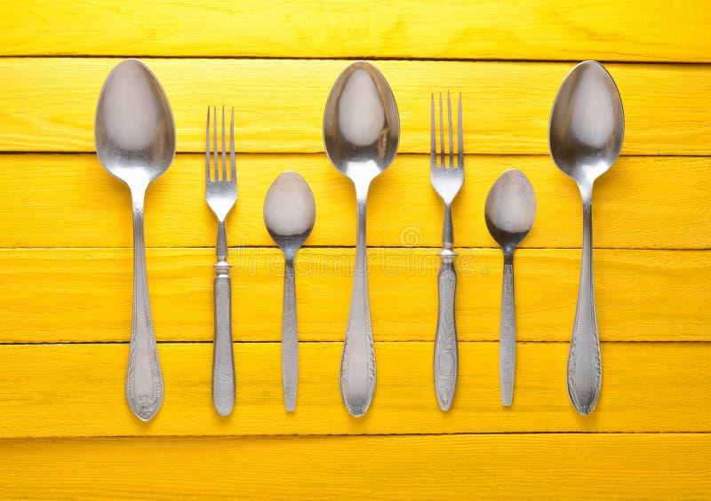 Un sistema de cucharas y de bifurcaciones en una tabla de madera amarilla foto de archivo libre de regalías