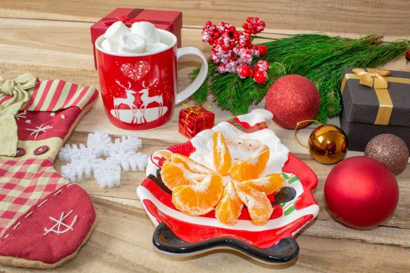 Un sistema de decoraciones de la Navidad - una placa en la forma de Papá Noel con las mandarinas, un calcetín para los regalos, u fotografía de archivo