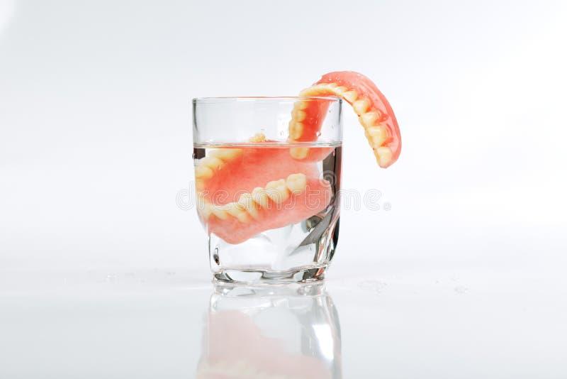 Un sistema de dentaduras en un vidrio de agua foto de archivo