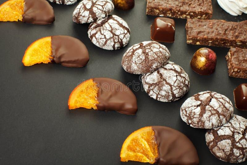 Un sistema de dulces hechos en casa: brownie, melcochas, galletas, mermelada, rebanadas deliciosas de naranja en chocolate y cara imagenes de archivo