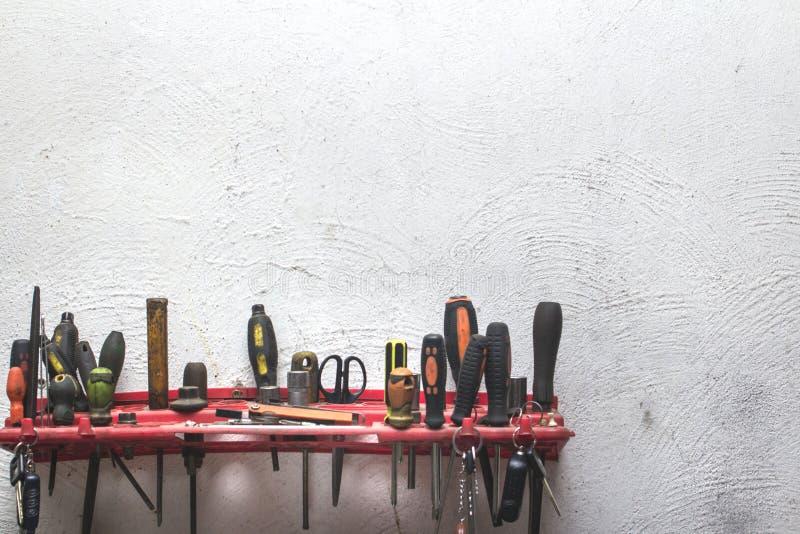 Un sistema de herramientas de trabajo de la construcción en una pared enyesada blanca imagenes de archivo