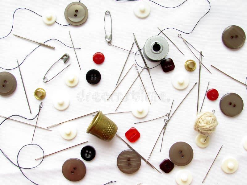 Un sistema de las agujas, dedales, botones, pernos, hilos de los colores negros y rojos que mienten en un fondo blanco brillante fotos de archivo libres de regalías
