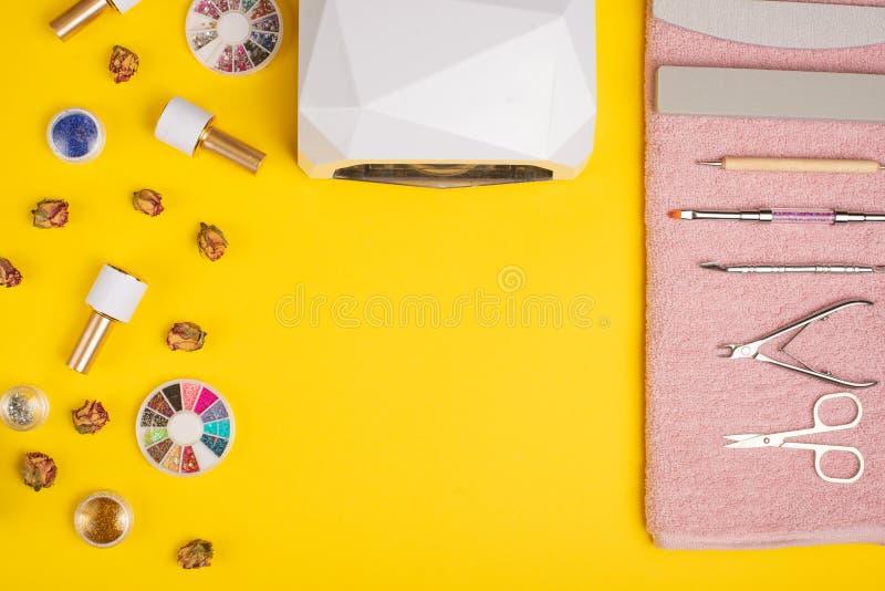 Un sistema de las herramientas cosméticas para la manicura y la pedicura en un fondo púrpura E fotografía de archivo