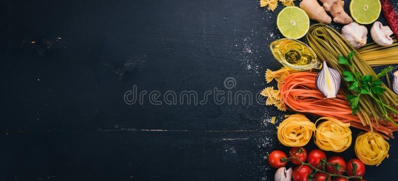 Un sistema de las pastas, tallarines, espaguetis, tallarines, fettuccine, Farfalle El cocinar italiano, verduras frescas y especi fotografía de archivo libre de regalías
