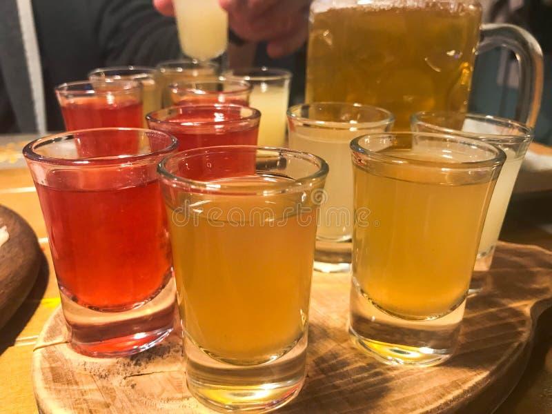 Un sistema de las porciones de los vidrios rojos amarillo-naranja deliciosos, tiros con el alcohol fuerte, vodka, brandy, brandy, fotos de archivo