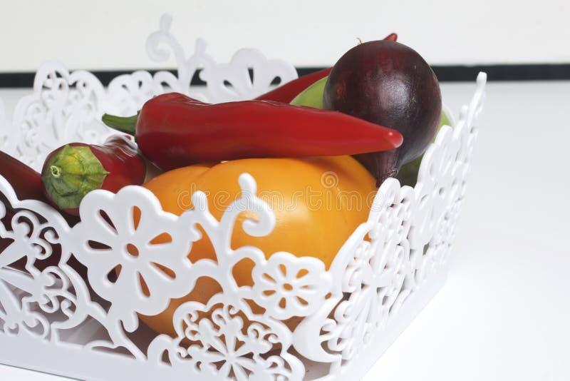 Un sistema de las verduras para la ensalada miente en una cesta del cordón En un fondo blanco Cebollas y tomates de diversos colo fotos de archivo