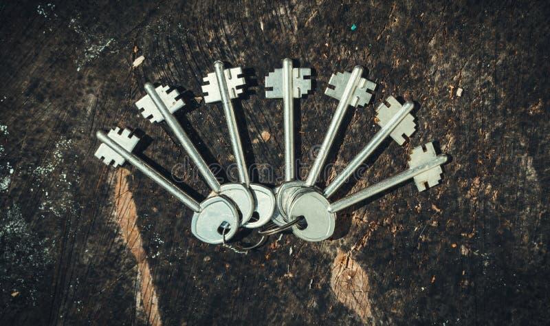 Un sistema de llaves pasadas de moda en un fondo de un tocón de madera viejo La decoración en estilo rústico imagen de archivo