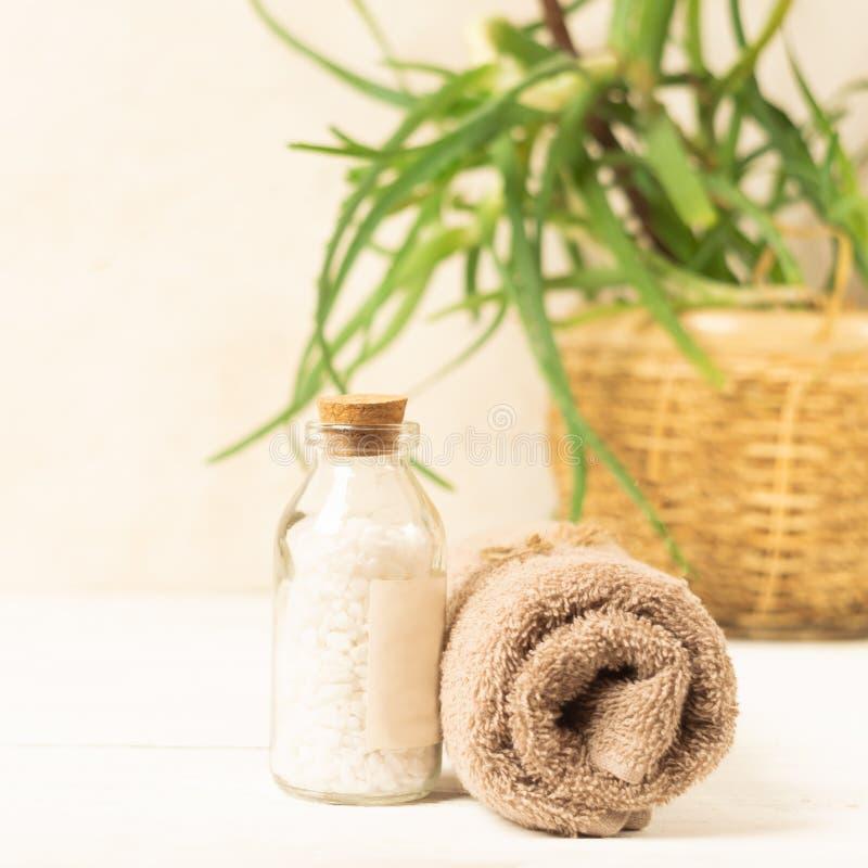 Un sistema de los artículos para los procedimientos del balneario Sal de baño, toalla en una belleza ligera del fondo y concepto  imagen de archivo libre de regalías