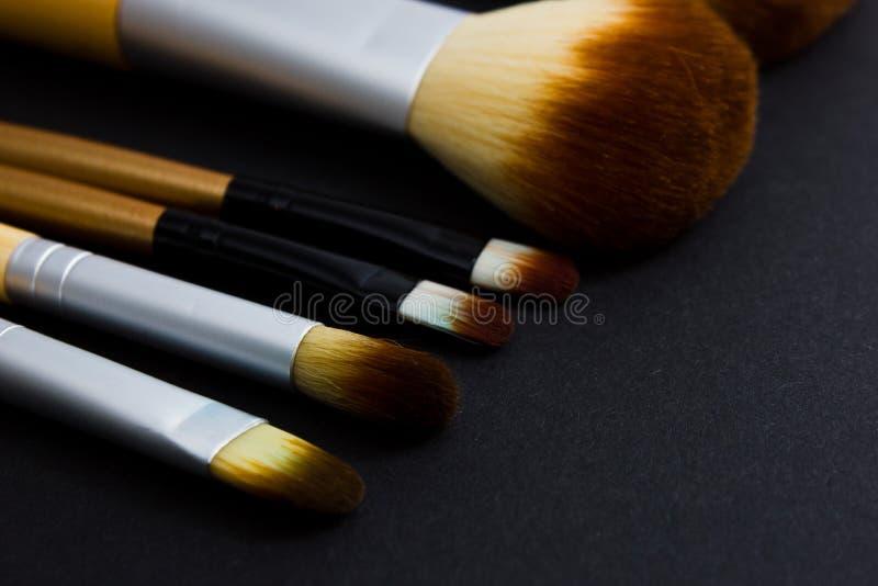 Un sistema de los cepillos para el maquillaje profesional en un fondo negro imagen de archivo