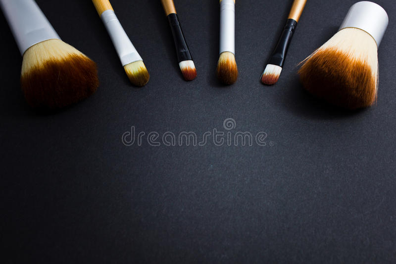 Un sistema de los cepillos para el maquillaje profesional en un fondo negro foto de archivo libre de regalías