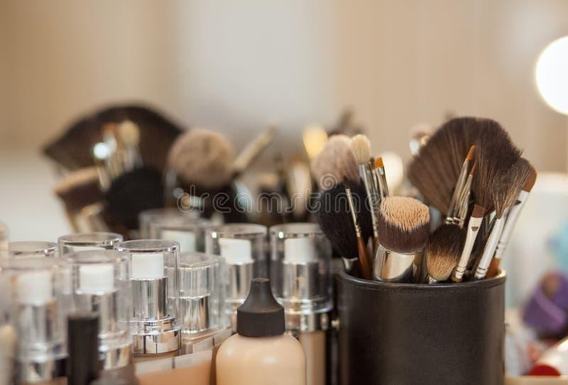 Un sistema de los cepillos para el maquillaje y entona la fundación para la persona que se coloca en la tabla delante de un espej imagenes de archivo