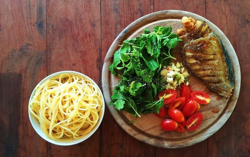 Un sistema de los ingredientes para cocinar los espaguetis con los pescados curruscantes secos y albahaca en la tabla de madera imágenes de archivo libres de regalías
