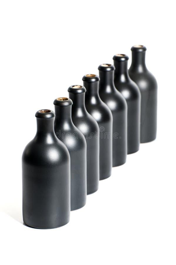 Un sistema de varias botellas negras vacías en un cierre blanco del fondo imagen de archivo