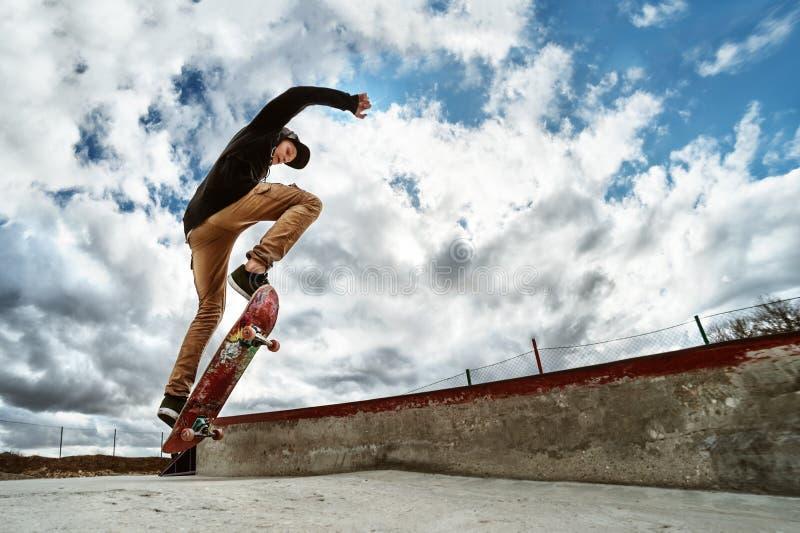 Un skater joven hace Wallie en un skatepark, saltando en un monopatín en el aire con un golpe fotos de archivo libres de regalías