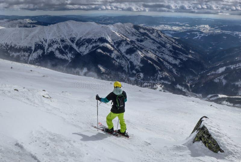Un skieur d'homme trouvant la meilleure voie pour le freeride Un skieur regardant vers le bas à la vallée Un casque jaune Bon mom photo libre de droits
