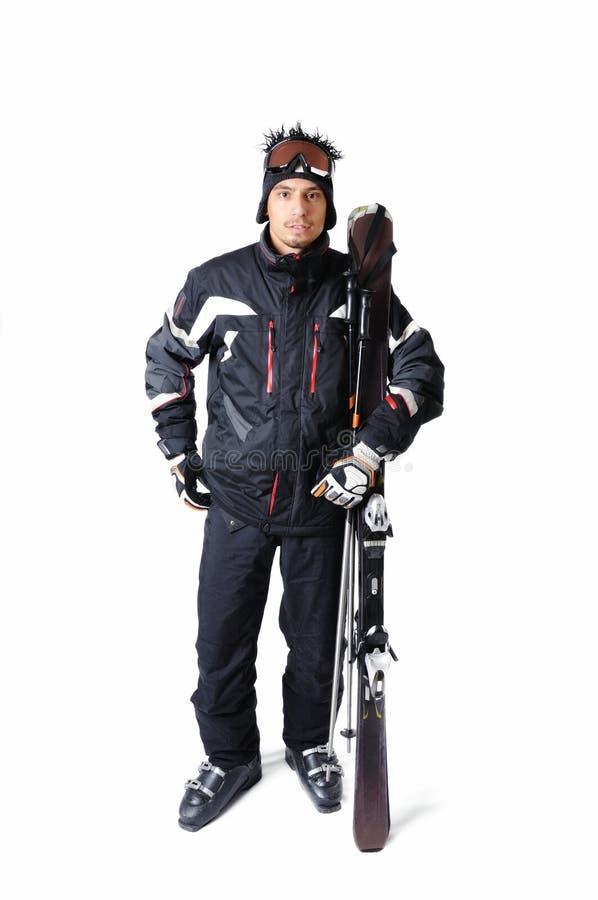 Un skieur masculin posant avec le plein équipement sur un fond blanc image libre de droits
