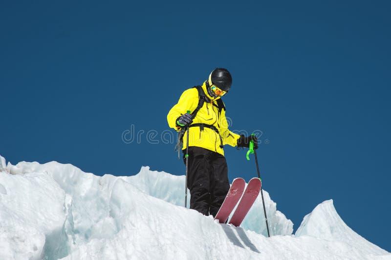 Un skieur parasitaire dans l'équipement complet se tient sur un glacier dans le Caucase du nord Skieur préparant avant de sauter  photographie stock libre de droits