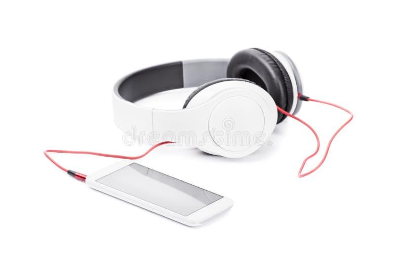 Un smart-téléphone s'est relié aux écouteurs d'isolement sur le fond blanc photographie stock
