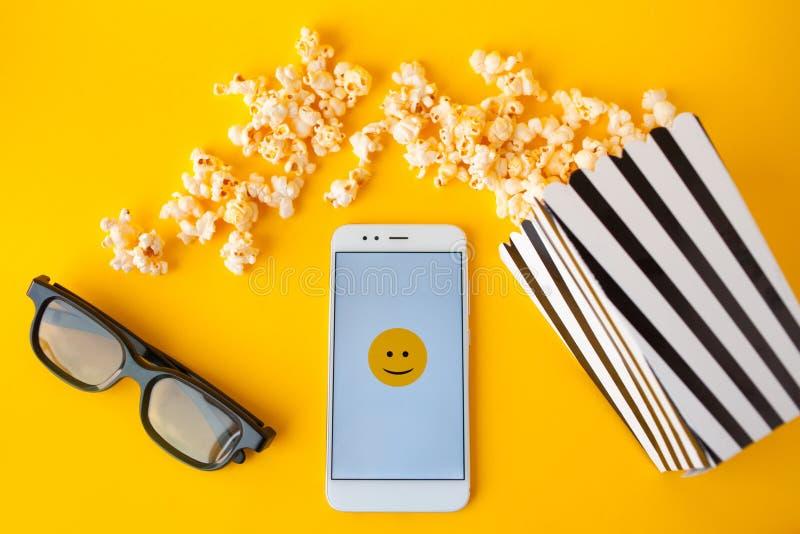 Un smartphone blanc avec des smilies sur l'écran, les verres 3d, une boîte de papier rayée noire et blanche et le maïs éclaté dis photographie stock
