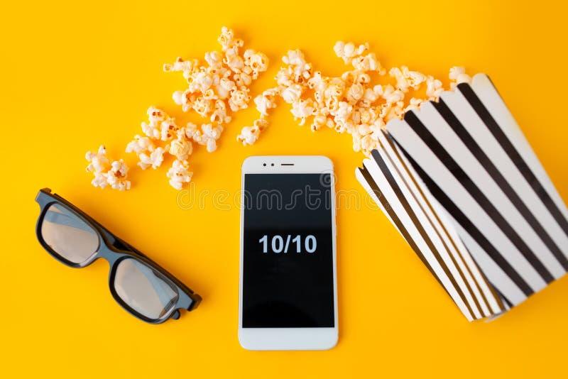 Un smartphone blanc avec des smilies sur l'écran, les verres 3d, une boîte de papier rayée noire et blanche et le maïs éclaté dis images libres de droits