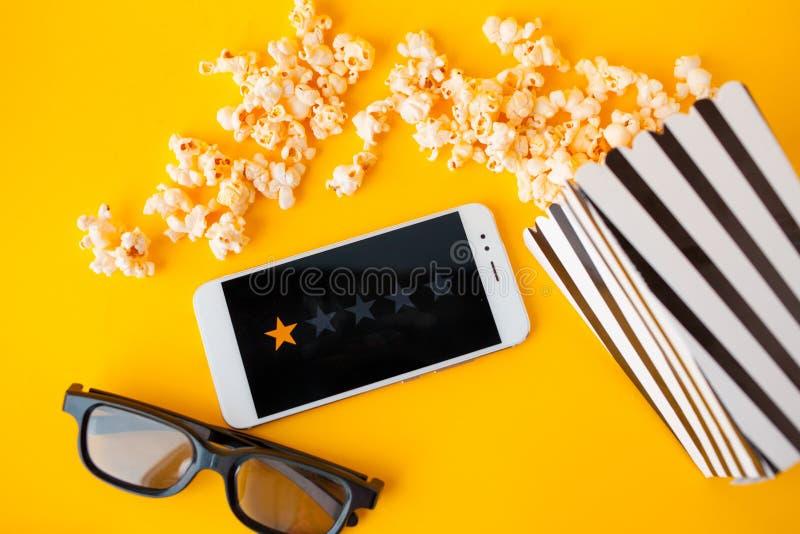 Un smartphone blanc avec des smilies sur l'écran, les verres 3d, une boîte de papier rayée noire et blanche et le maïs éclaté dis photo libre de droits