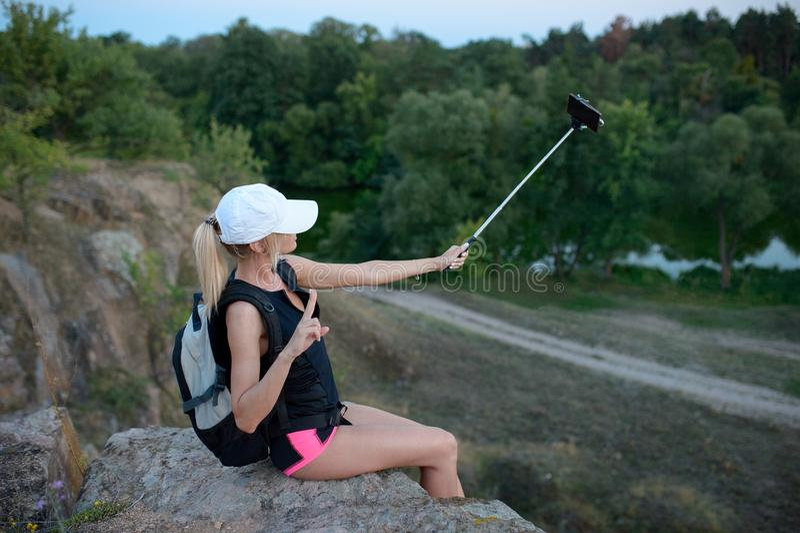 Un smartphone d'utilisation de randonneur de jeune femme dehors photos stock