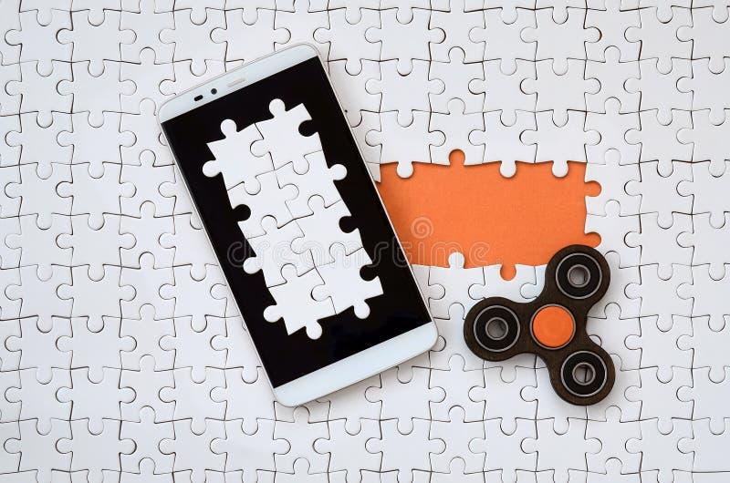 Un smartphone grande moderno con una pantalla táctil y un hilandero mienten en un rompecabezas blanco en un estado montado con lo foto de archivo