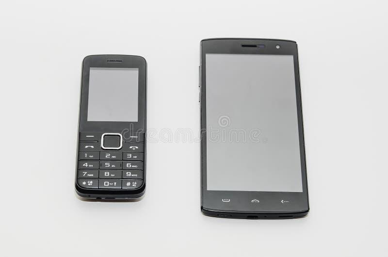 Un smartphone moderne et un vieux téléphone portable classique côte à côte sur un fond blanc photos stock