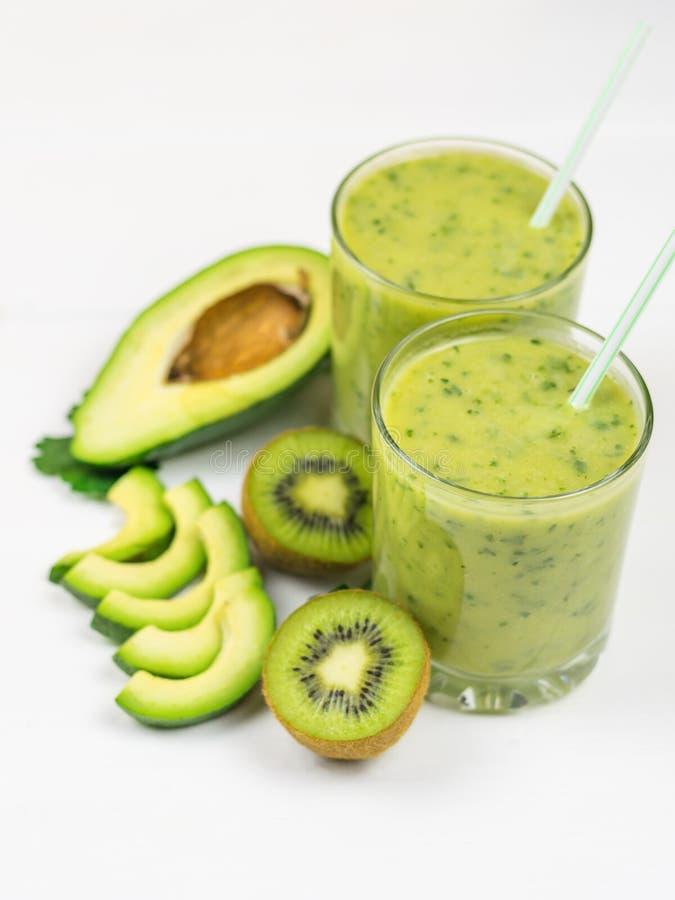 Un smoothie recién preparado del aguacate, del plátano, de la naranja, del limón y del kiwi en una tabla blanca Comida del vegeta imagen de archivo