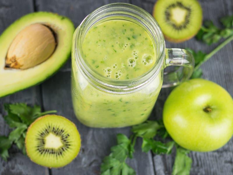 Un smoothie recién preparado del aguacate, del plátano, de la naranja, del limón y del kiwi en una tabla de madera Comida del veg foto de archivo libre de regalías