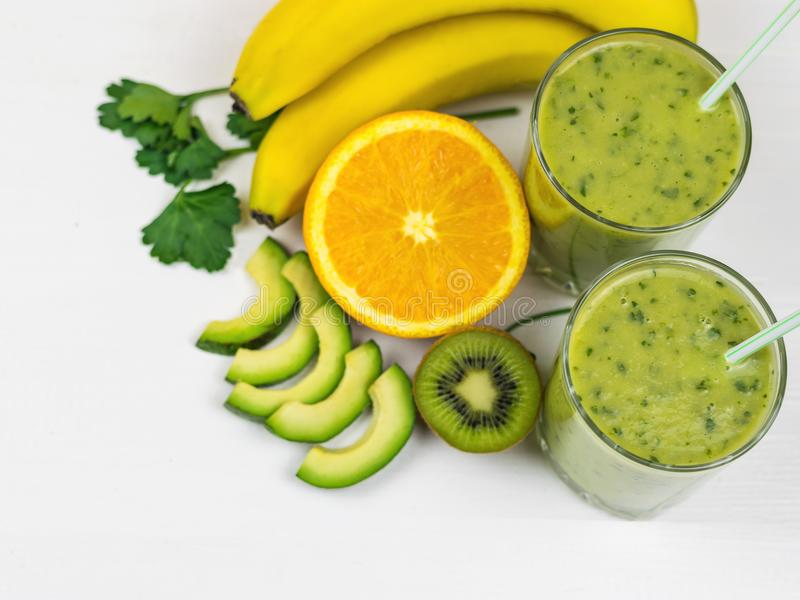 Un smoothie recién preparado del aguacate, del plátano, del perejil, del limón y del kiwi en una tabla de madera blanca Comida de imagen de archivo