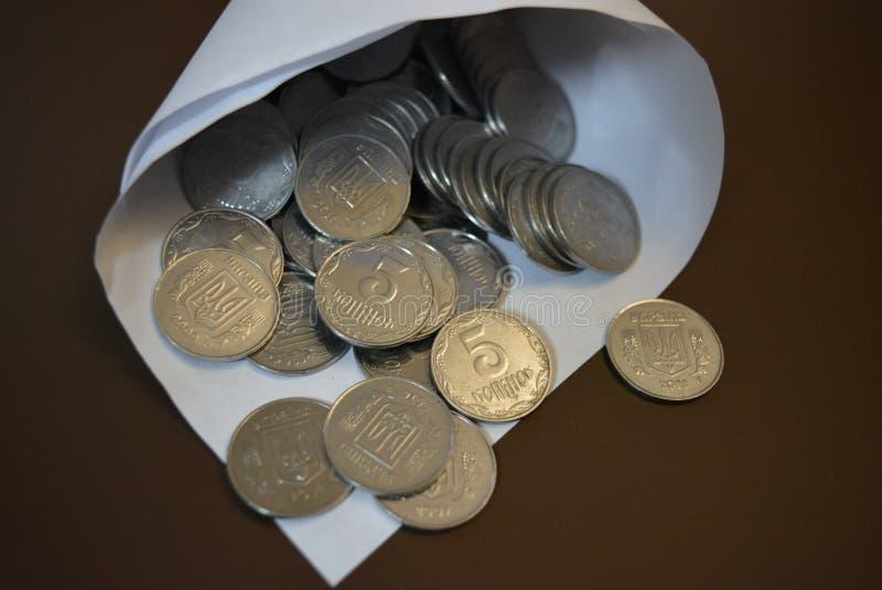 Un sobre con el dinero, en un bolso del Libro Blanco es pequeño dinero, peniques ligeros blancos del metal, ahorros del efectivo  fotografía de archivo libre de regalías