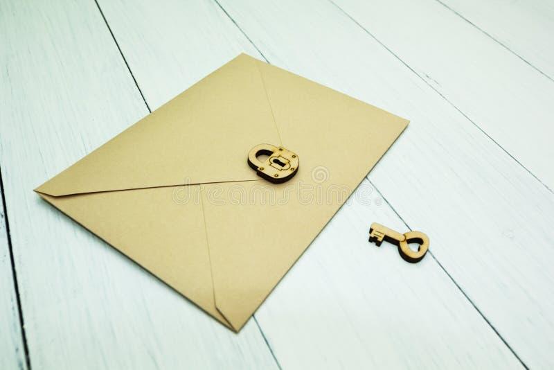Un sobre de papel del correo es cerrado con una cerradura al lado de la llave en una tabla blanca, un secreto foto de archivo libre de regalías