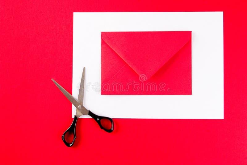 Un sobre rojo con las tijeras fotos de archivo libres de regalías