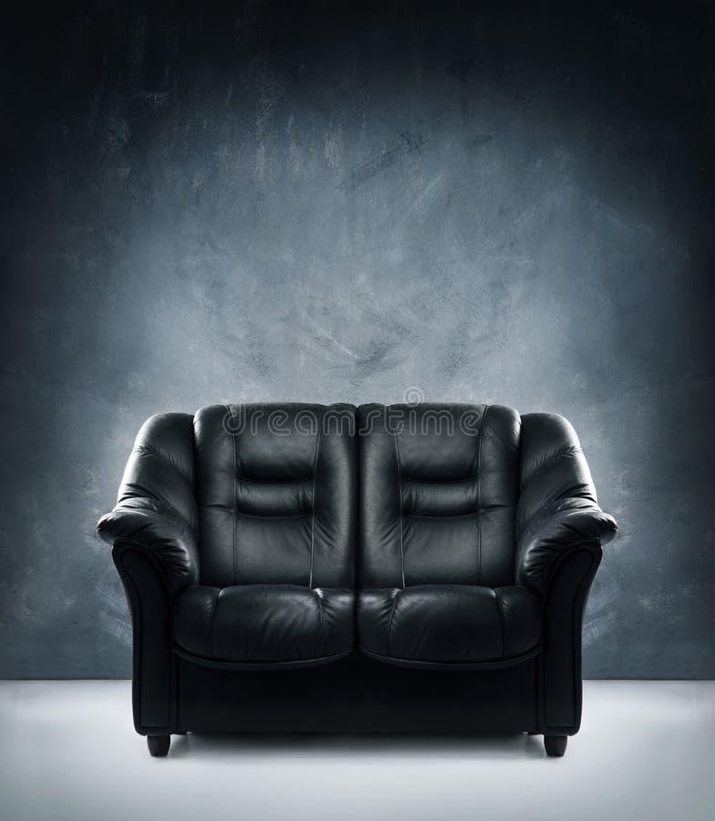 Un sofa en cuir noir sur un fond grunge foncé photo stock