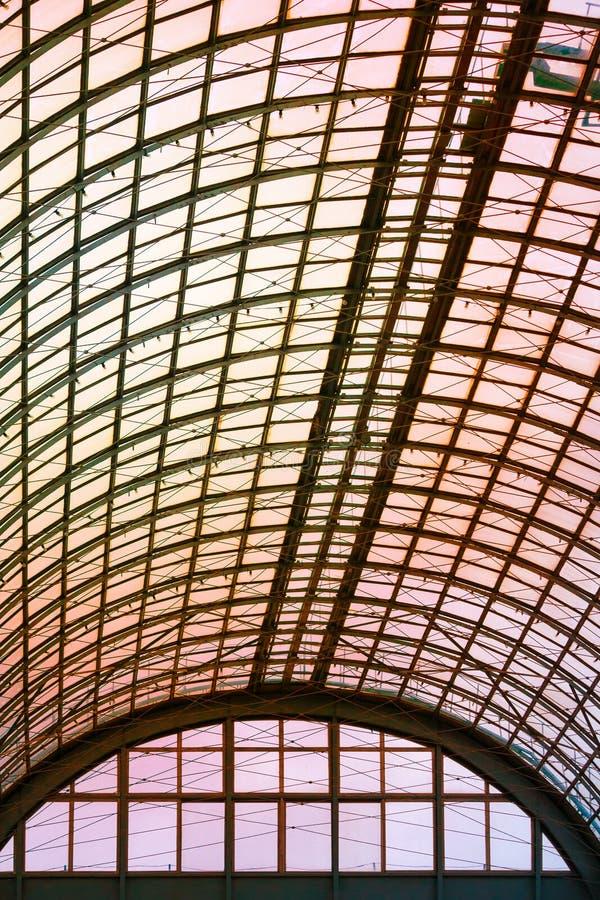 Un soffitto emisferico di vetro e di metallo in costruzione moderna su un fondo di luce solare arancio fotografia stock libera da diritti