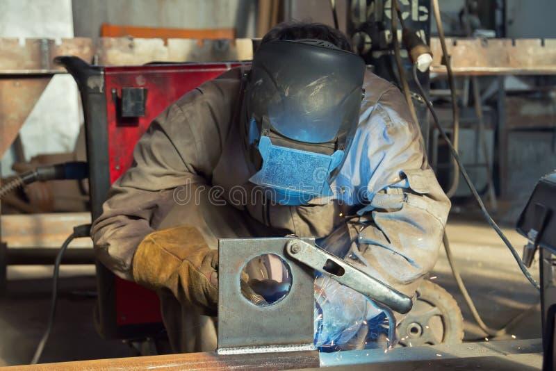 Un soldador fabrica las estructuras de acero usando weldin semiautomático foto de archivo libre de regalías