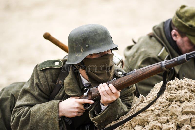 Un soldato tedesco in una fossa con un fucile in sua mano Rievocazione storica della battaglia immagine stock