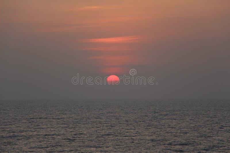 Un sole rosso luminoso ha spleso l'ampio, mare luccicante fotografie stock