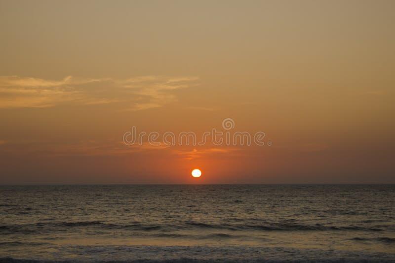Un soleil orange dans un ciel rose gris pourpre de coucher du soleil dans la perspective de l'océan photographie stock