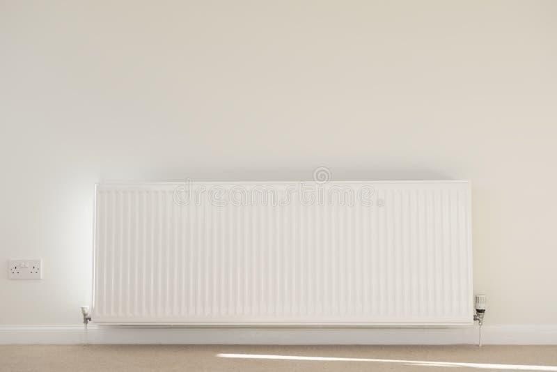 Un solo blanco del solo radiador en alfombra y la pared neutrales del fondo del salón para la calefacción de casa imágenes de archivo libres de regalías