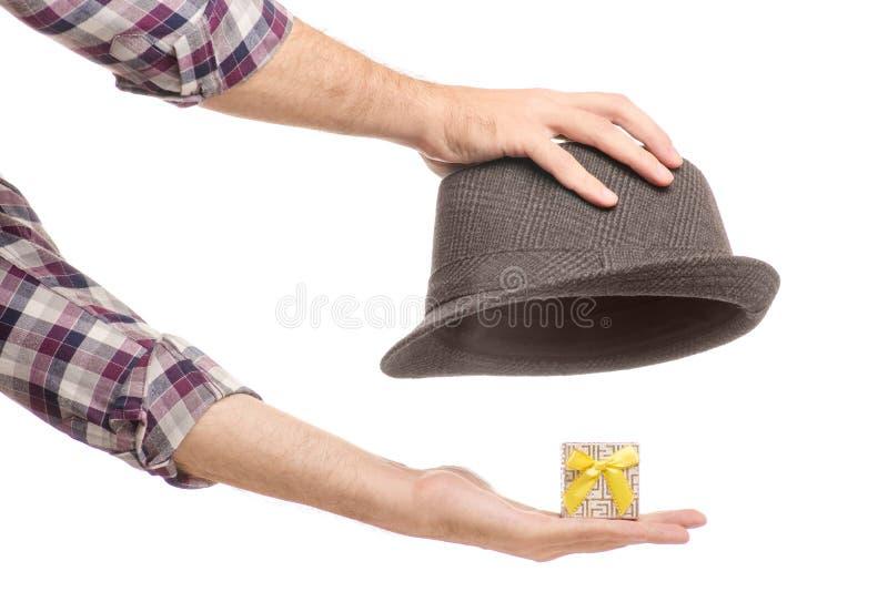 Un sombrero con una caja de regalo de una mano del ` s del hombre foto de archivo
