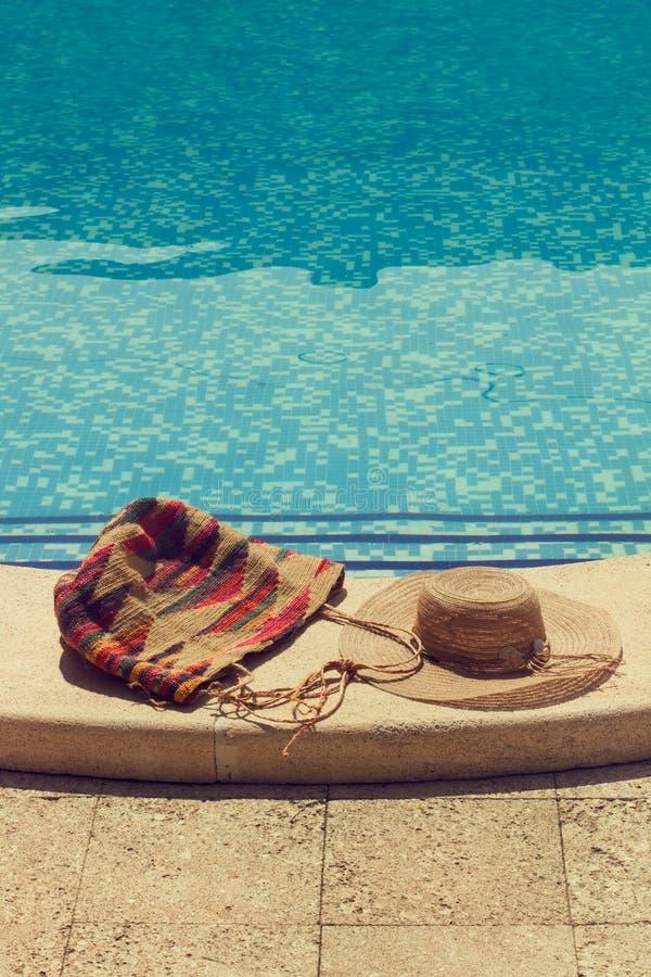 Un sombrero de paja y un bolso en la piscina imagenes de archivo