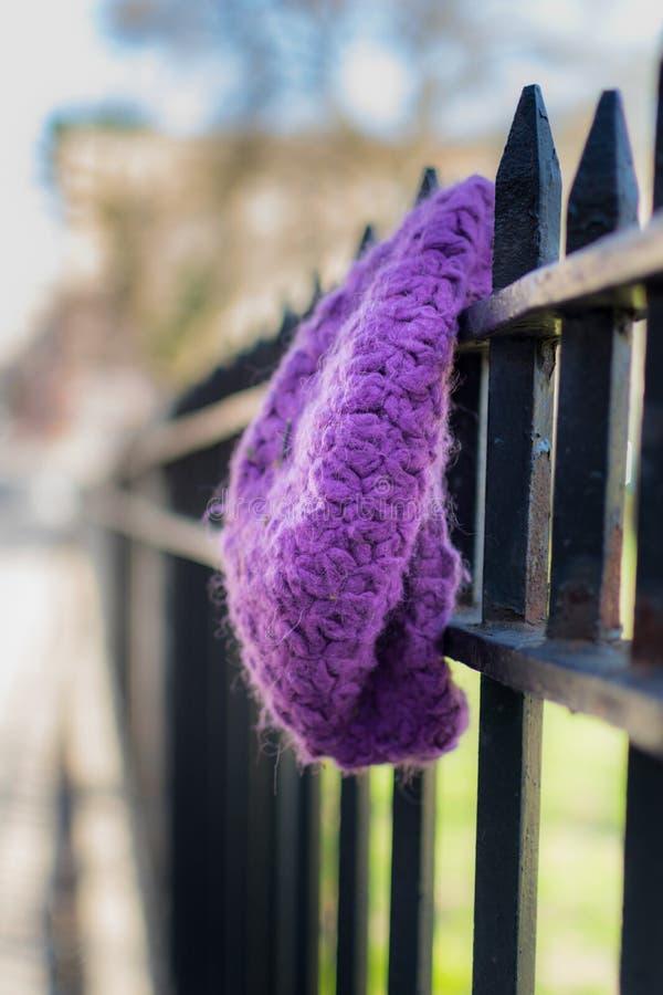 Un sombrero púrpura perdido y olvidado, hecho punto que cuelga en una cerca del arrabio  foto de archivo libre de regalías