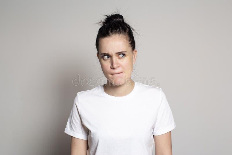 Un songeur, doutant de la jeune femme a pincé ses lèvres et regards soupçonneusement au côté Sur un fond blanc photo libre de droits