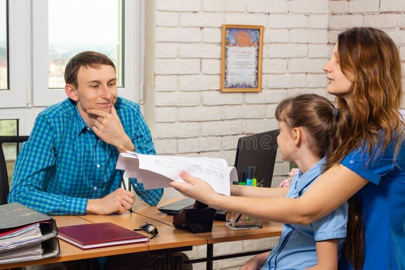 Un spécialiste en bureau refuse de faire un recalcul des factures quand une mère de beaucoup d'enfants vient chez la réception image stock