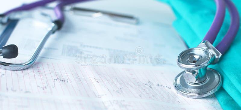 Un stéthoscope formant un coeur et un presse-papiers sur un uniforme médical, plan rapproché photos stock