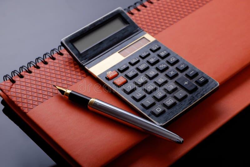 Un stylo-plume, un livre de calculatrice et de chèque ou un carnet photo stock