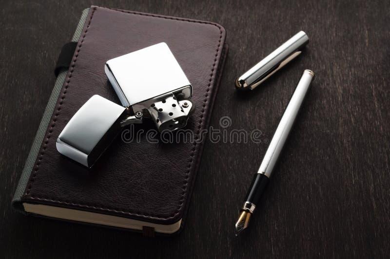 Un stylo-plume, un vieil allumeur, un carnet sur une table foncée photo libre de droits