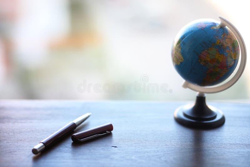 Un stylo sur le bureau et un petit globe images libres de droits
